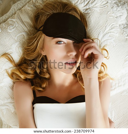 Portrait of a beautiful young blonde girl lying on a bed wearing a mask to sleep - stock photo