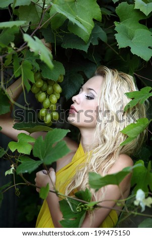 portrait of a beautiful young blonde with a bunch of grapes
