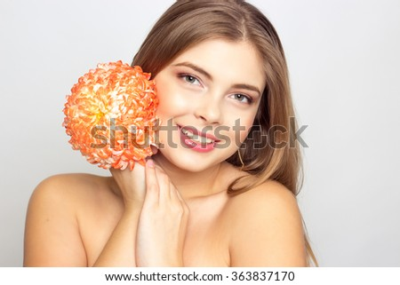 Portrait of a beautiful young blonde woman, holding a flower. International Women's Day.