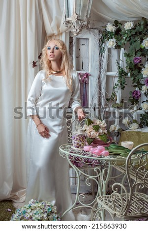 Portrait of a beautiful young blonde woman in a white dress in a room where a lot of flowers - stock photo