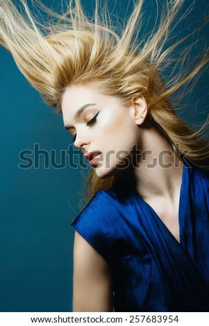 Portrait of a beautiful young blonde woman in studio on a blue background with developing hair, the concept of beauty