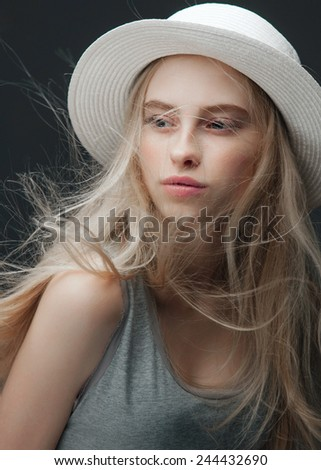 Portrait of a beautiful young blonde woman in white hat in the studio - stock photo