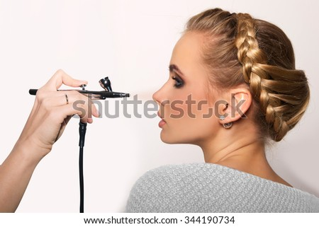 portrait of a beautiful young blonde woman on a light background. there is hand with aerograph making an airbrush make up. hair tied in a braid. copy space. - stock photo
