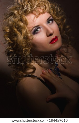 Portrait of a beautiful young blonde woman with curly hair in lingerie posing in the shadows