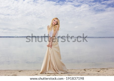Portrait of a beautiful young blonde woman with wavy hair in nature. Girl posing on the beach, standing on the sand near the water