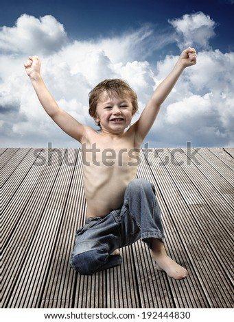 Portrait of a beautiful young boy sitting in happy pose on a wooden floor against cloudy blue sky - stock photo