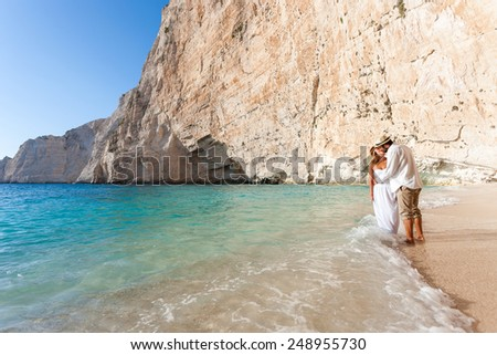 portrait of a beautiful young bride and groom at the beach - stock photo