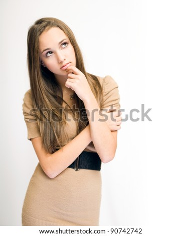 Portrait of a beautiful young brunette girl in pondering gesture. - stock photo