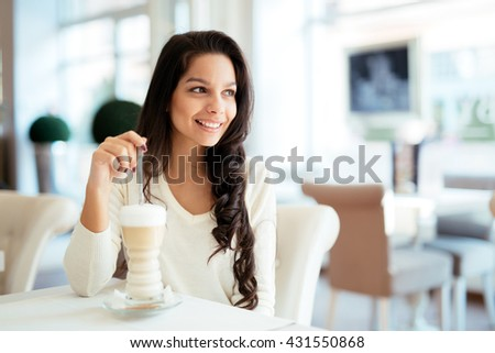 Portrait of a beautiful young brunette in cafe drinking coffee - stock photo