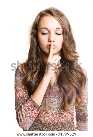 Portrait of a  beautiful young brunette making hush gesture. - stock photo