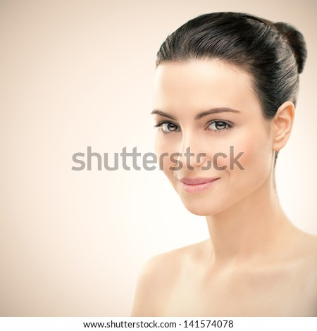 Portrait of a beautiful young brunette posing in front of a pink background. - stock photo