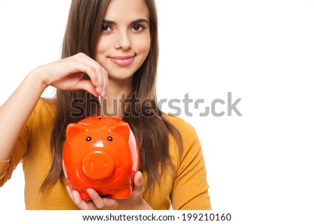 Portrait of a beautiful young brunette posing with colorful piggy bank.