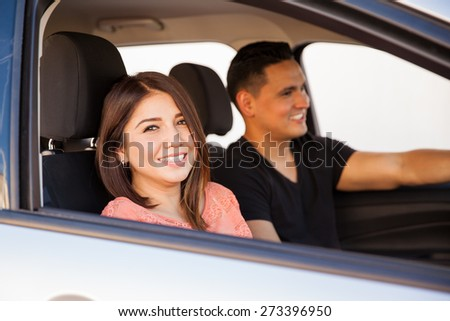 Portrait of a beautiful young brunette sitting in the passenger seat of a car and having some fun with her boyfriend - stock photo