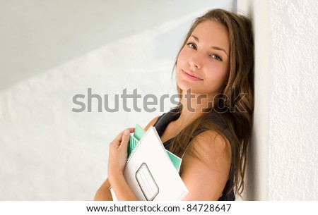 Portrait of a beautiful young brunette student girl holding exercise books. - stock photo