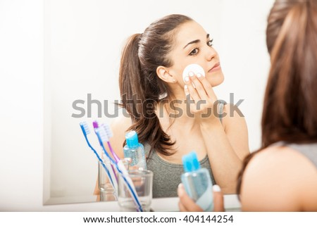 Portrait of a beautiful young brunette using a cotton pad to remove her makeup in the bathroom at night - stock photo