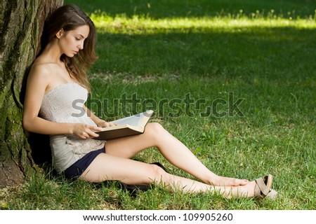 Portrait of a beautiful young brunette woman enjoying book outdoors.