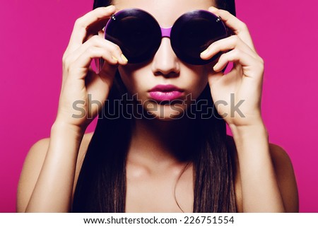 Portrait of a beautiful young brunette woman on a pink background in studio with sunglasses