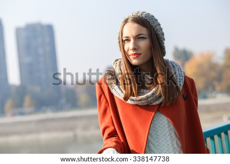 Portrait of a beautiful young brunette woman on the bridge, she is looking at distance.