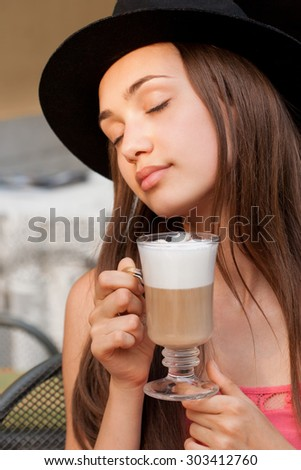 Portrait of a beautiful young brunette woman sitting outdoors in coffee shop. - stock photo