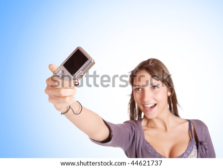 Portrait of a beautiful young brunette woman talking a picture with a digital camera