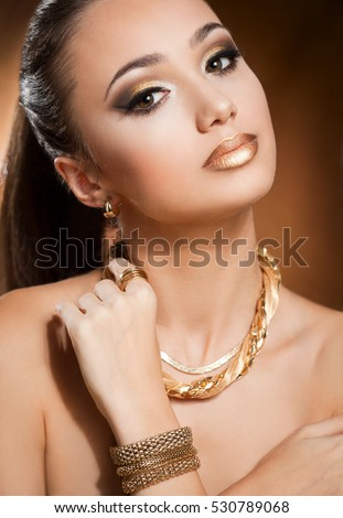Portrait of a beautiful young brunette woman wearing gold jewelry.