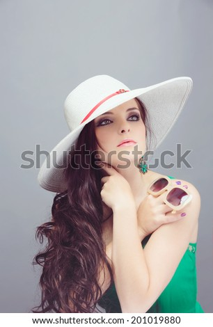 Portrait of a beautiful young brunette woman. Wearing white hat over long loose curly hair. Open shoulders summer emerald green dress. Against grey studio background.  - stock photo