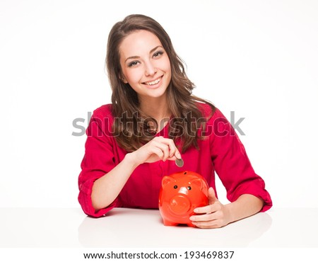 Portrait of a beautiful young brunette woman with colorful piggy bank.