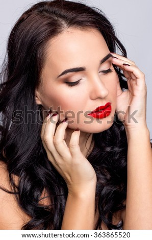 Portrait of a beautiful young brunette woman with red lipstick on a white background. Valentine's Day.