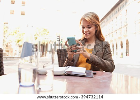 Portrait of a beautiful young business woman at a coffee shop terrace holding smart phone working, smiling outdoors. Professional woman in city using technology. Smart girl lifestyle, sunny exterior. - stock photo
