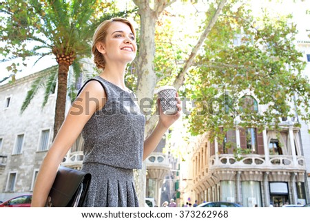 Portrait of a beautiful young business woman commuter walking in classic buildings city, holding a coffee cup and walking. Professional businesswoman drinking coffee, on the go lifestyle exterior.