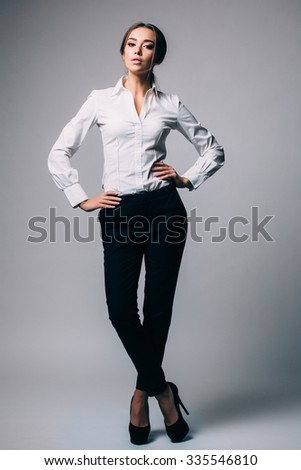 Portrait of a beautiful young business woman standing against grey background - stock photo