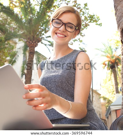 Portrait of a beautiful young business woman using a laptop computer in a sunny park, smiling and looking, outdoors. Professional businesswoman wearing spectacles, aspirational lifestyle exterior. - stock photo