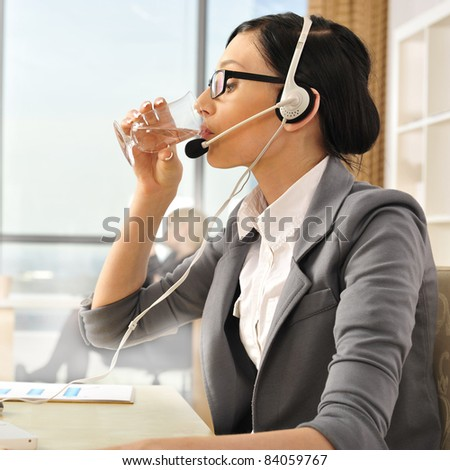 Portrait of a beautiful young businesswoman drinking water. Office background. - stock photo