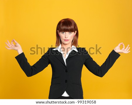 portrait of a beautiful, young businesswoman, having a break and meditating, on yellow background - stock photo