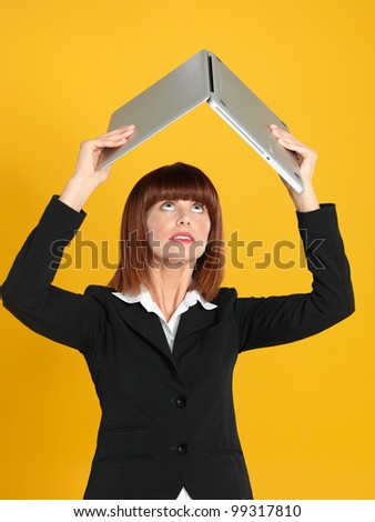 portrait of a beautiful, young businesswoman, holding a laptop above her head as a shelter, on yellow background