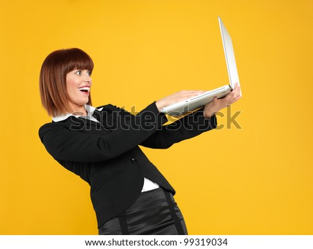 portrait of a beautiful, young businesswoman, holding a laptop, witn a surprised face expression, on yellow background - stock photo