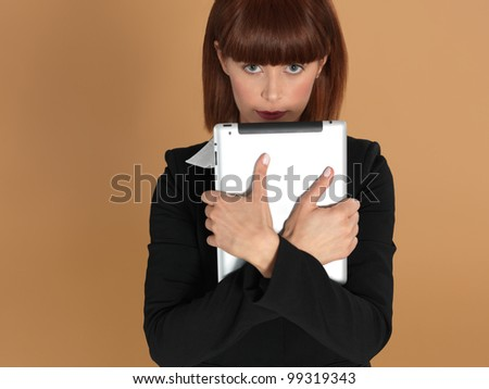 portrait of a beautiful, young businesswoman, holding an electronic computer pad, smiling, on beige background