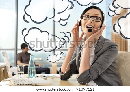 Portrait of a beautiful young businesswoman on the phone and happy. Office background. Blank dialog cloud balloons around her - stock photo