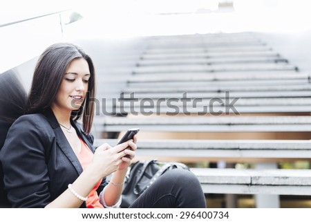Portrait of a beautiful young businesswoman standing outside using mobile phone - stock photo