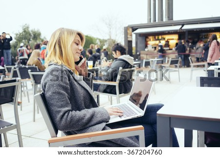 Portrait of a beautiful young businesswoman who is holding portable laptop computer while sitting in a coffee shop outdoors and talking on the cell-phone - stock photo