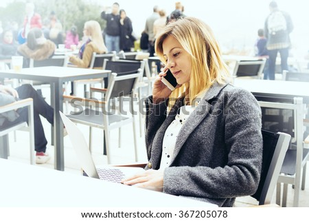 Portrait of a beautiful young businesswoman who is holding portable laptop computer while sitting in a coffee shop outdoors and talking on the smart-phone - stock photo