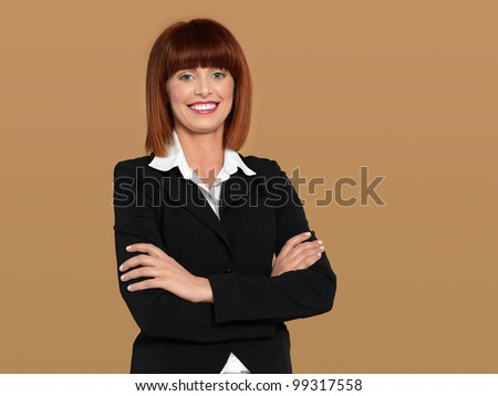 portrait of a beautiful, young, businesswoman, with her arms crossed, on beige background - stock photo