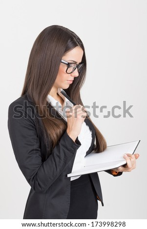 Portrait of a beautiful young Caucasian brunette businesswoman with notebook wearing black suit and eyeglasses. Business people of student. - stock photo