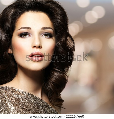 Portrait of a Beautiful young caucasian sexy woman with brown curly hairs. Pretty fashion model with dark brown eye makeup - stock photo
