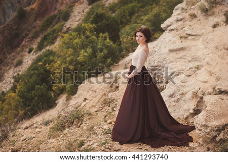 Portrait of a beautiful young caucasian stylish woman in evening gown standing on the background of spectacular nature, rock and trees, in sunlight - stock photo