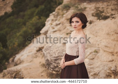 Portrait of a beautiful young caucasian stylish woman in evening gown standing on the background of spectacular nature, rock and trees, in sunlight