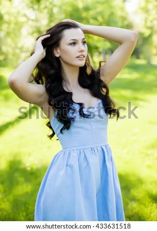 Portrait of a beautiful young Caucasian woman in a spring garden. Sweet girl, clean skin, long dark hair. - stock photo