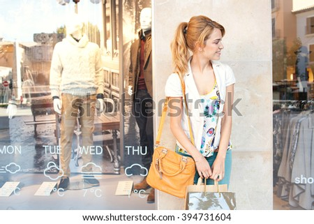 Portrait of a beautiful young consumer woman in city leaning on a stone wall, relaxing with shopping bags by a fashion store window, smiling outdoors. Tourist recreation lifestyle, exterior. - stock photo