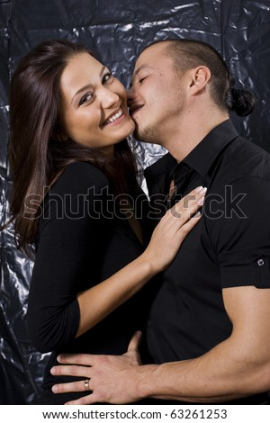 Portrait of a beautiful young couple about to kiss against black background