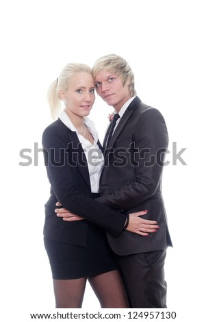 Portrait of a beautiful young couple hugging each other against grey background